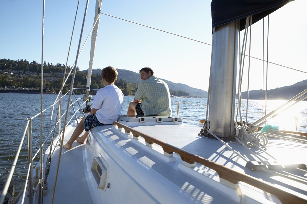 View of a father and son on the deck of a sailboat